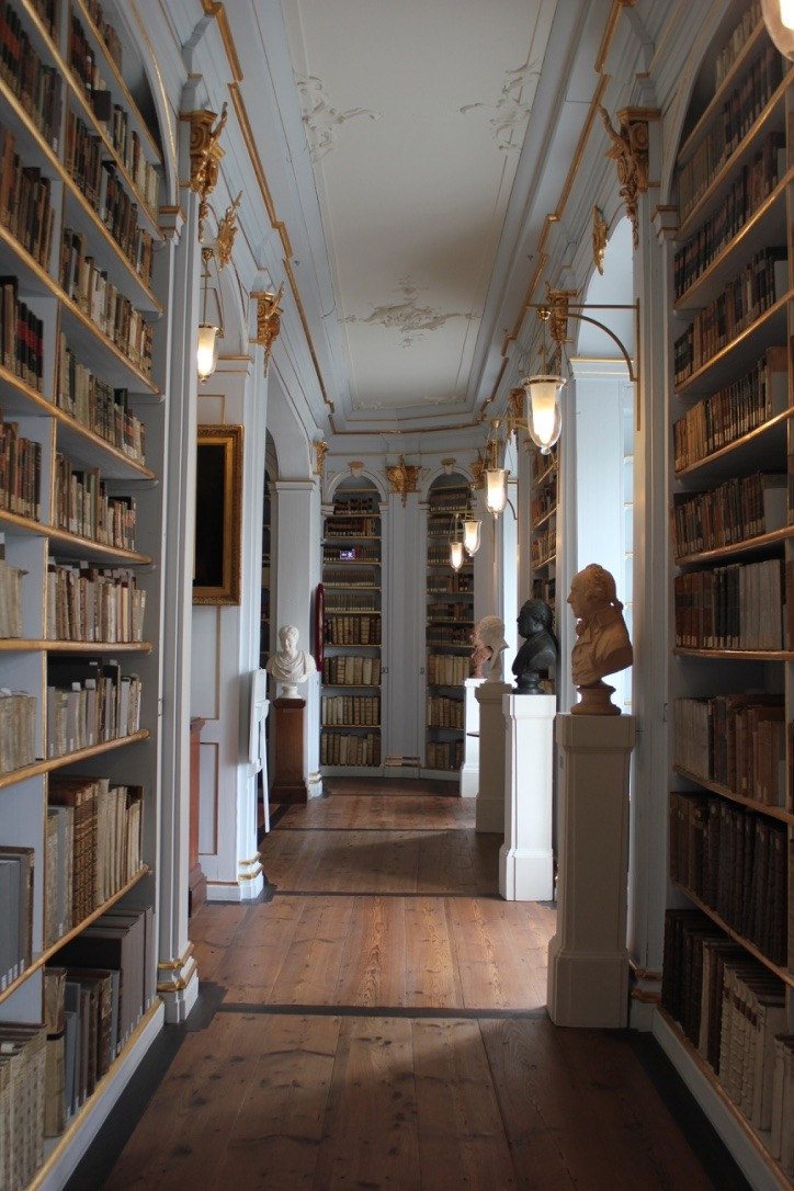 One of the corridors of the famous library, lined with book shelves and busts of famous thinkers.