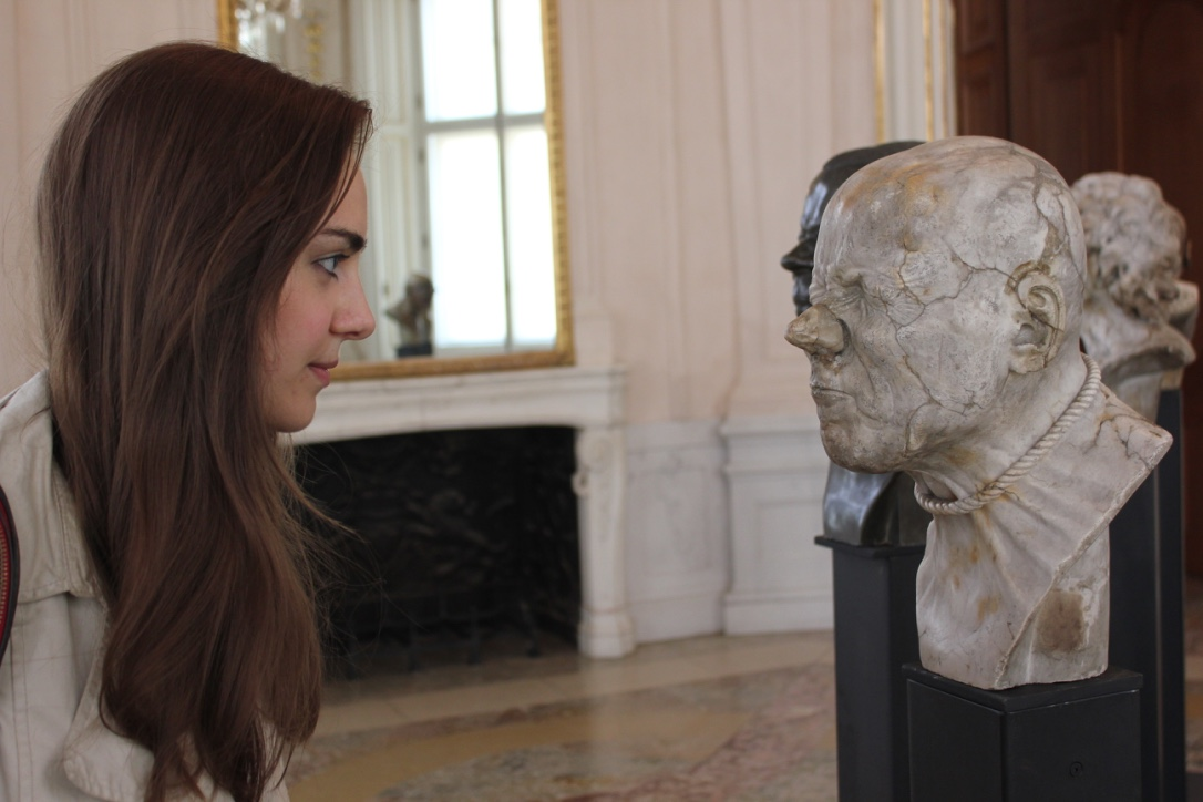 The picture displays author Sheila in front of one of Messerschmidt's busts at belvedere.