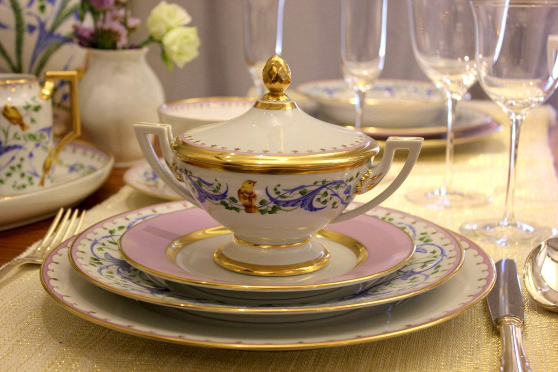 A table with beautifully decorated Augarten porcelain plates and items. They show soft colors: Pink, gold and blue. On it, there is a fine ornamental pattern with birds painted. The golden boarders of the plates shimmer.